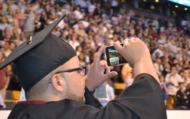 Graduating senior taking a video on his cell phone at the TD Garden