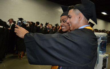 Two students pose for a selfie before the commencement exercises at the TD Garden