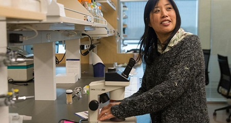 Graduate Program Director Linda Huang testing out a microscope in her lab in the Integrated Sciences Complex.