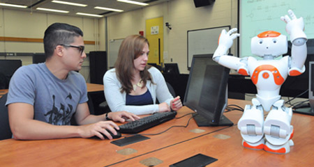 Two UMass Boston computer engineering students work with a robot