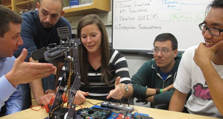 Four UMass Boston computer engineering students work with a robot