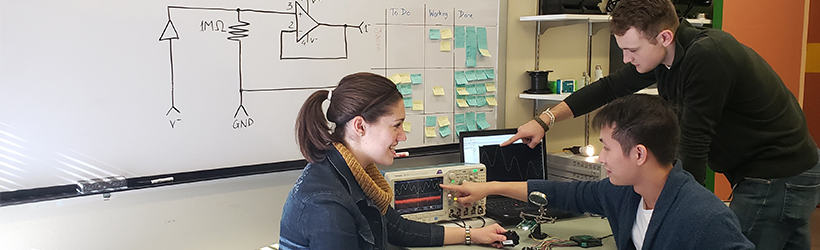 Teacher helps student with at an engineering computer station at UMass Boston.