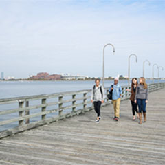 Four students walking in Quincy. You can see the UMass Boston campus behind them.