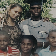Photograph of a man in uniform surrounded by a woman and three children