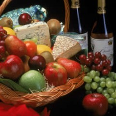 basket of wine, cheese and fruits.