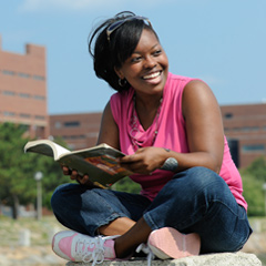 Smiling UMass Boston student reading a book on campus