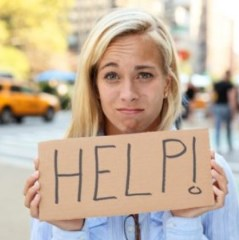 girls holding help sign looking sad