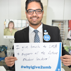 Staff member Shubi Joshi holds up a sign that says I give back to UMB to support all the future student leaders #whyigive2umb