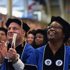 PhD students, dressed in commencement regalia, clapping