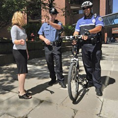 A woman meets with two public safety officers. One has a bike.