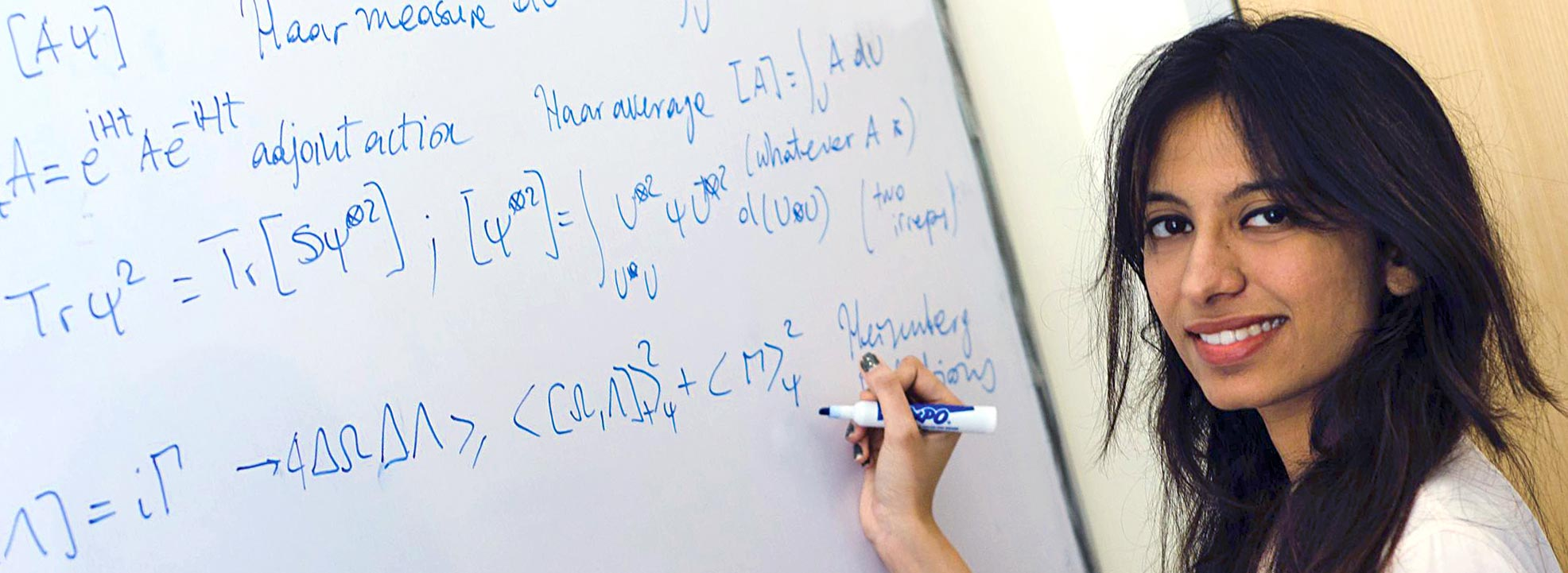 Graduate physics student holding a magic marker in front of mathematical formulas on whiteboard