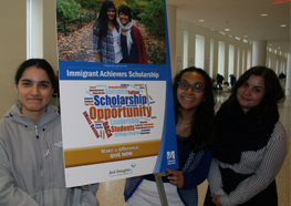 Three students standing in front of a poster for the Immigrant Achievers Scholarship