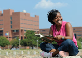 UMass Boston student studying outside, laughing with a book open