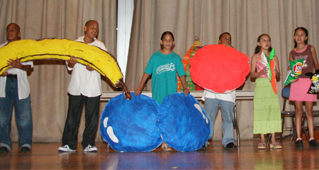Students holding up larger-than-life fruits.