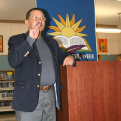 Man standing at a podium that says Hispanic Writers Week