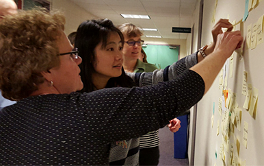 Faculty working together at a workshop putting sticky notes on a wall