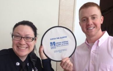 Diane Kirkpatrick and Justin Comeau hold up a frisbee that says Catch the Alerts! UMass Boston Alert System.