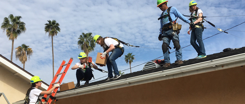 Students helping on a roof.