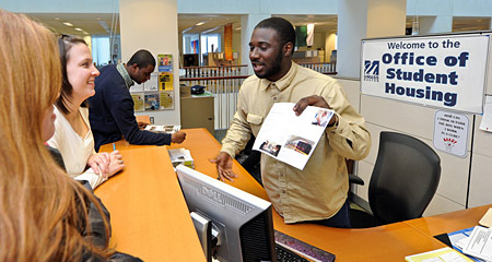 A staff member at the Office of Student Housing shows students information on apartment options.