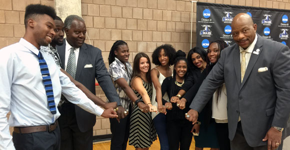 Members of UMass Boston's 2013-14 track and field teams receive their Little East Conference rings.
