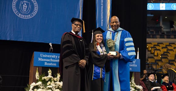 Provost Winston Langley, left, and Chancellor J. Keith Motley, right, present the JFK Award to July Suarez '15.