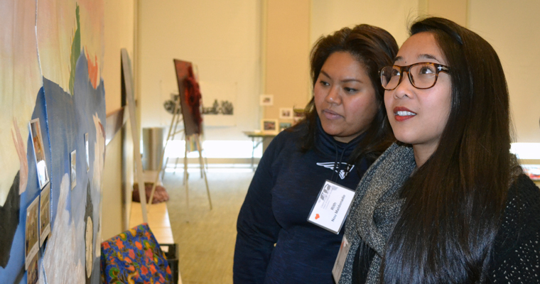 Rith Nou Maldonado '12 and Soramy Le '12 check out current student work at a 30th anniversary celebration for the Asian American Studies Pro