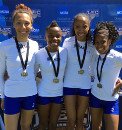 The members of the women's 4x100 relay team with their first place medals