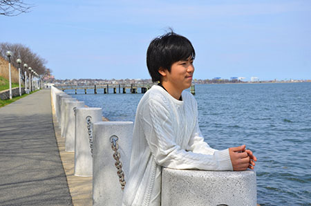 Keishiro Ota takes in the view along the HarborWalk on campus. Photo by: Cassandra Baptista