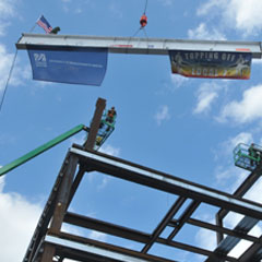 The final beam for General Academic Building No. 1 is raised into place.