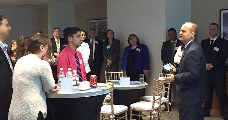 Dean Jorge Haddock (right) speaks to potential students at a Get Down to Business event at the UMass Club.