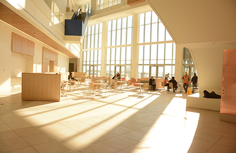 Students gather in the lobby of University Hall, which is bathed in light on a sunny day