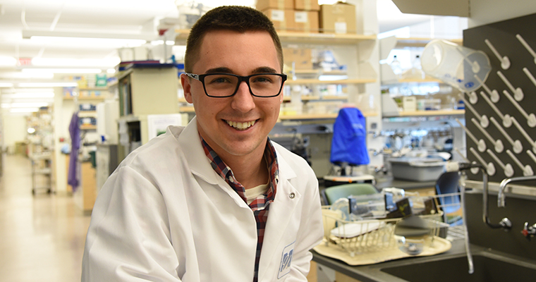 Photo of Alex Winnett in a UMass Boston laboratory
