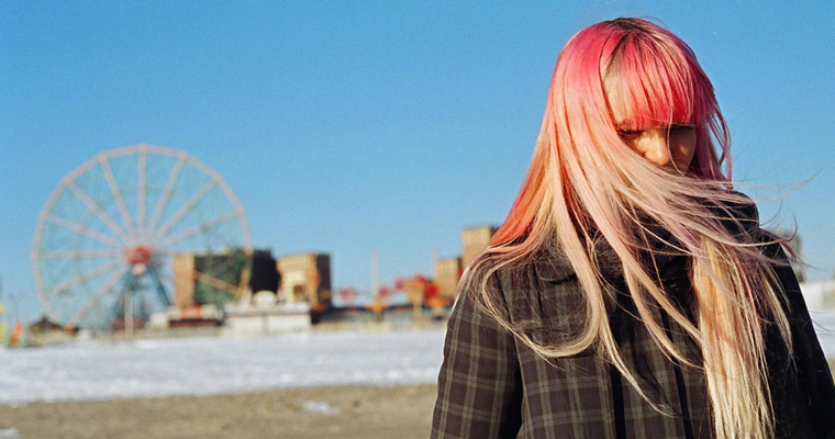 Image from All This Panic shows a girl in front of a ferris wheel