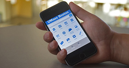 A hand holds a smart phone displaying the UMass Boston mobile app