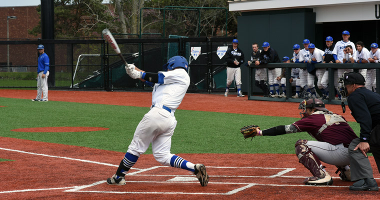 UMass Boston batter takes a swing while the UMass Boston bench looks on from the dugout at Monan Park