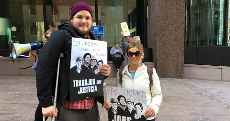 Juan Pablo Blanco and another student hold signs that say Jobs with Justice