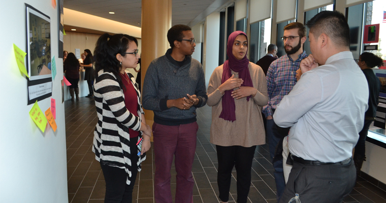 UMass Boston Honors College students explain their research findings to Boston Public Schools Superintendent Tommy Chang.