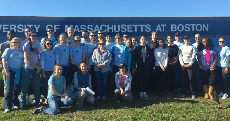 COASTSWEEP volunteers stand in front of the UMass Boston sign
