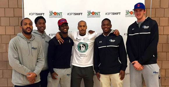 Dana Barros (center) with members of UMass Boston's men's basketball team