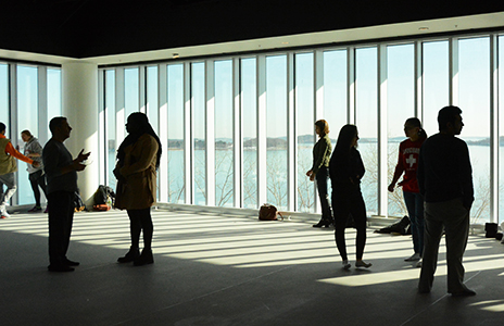 Students inside the dance studio at University Hall are silhouetted against a view of the Boston Harbor.