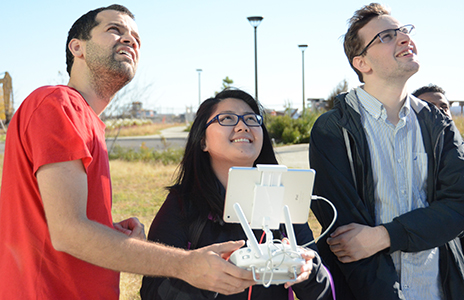 Senior biology major Phuong Le operates the remote control device for a drone while Dan Jaffe and Etienne Cartolano look on.