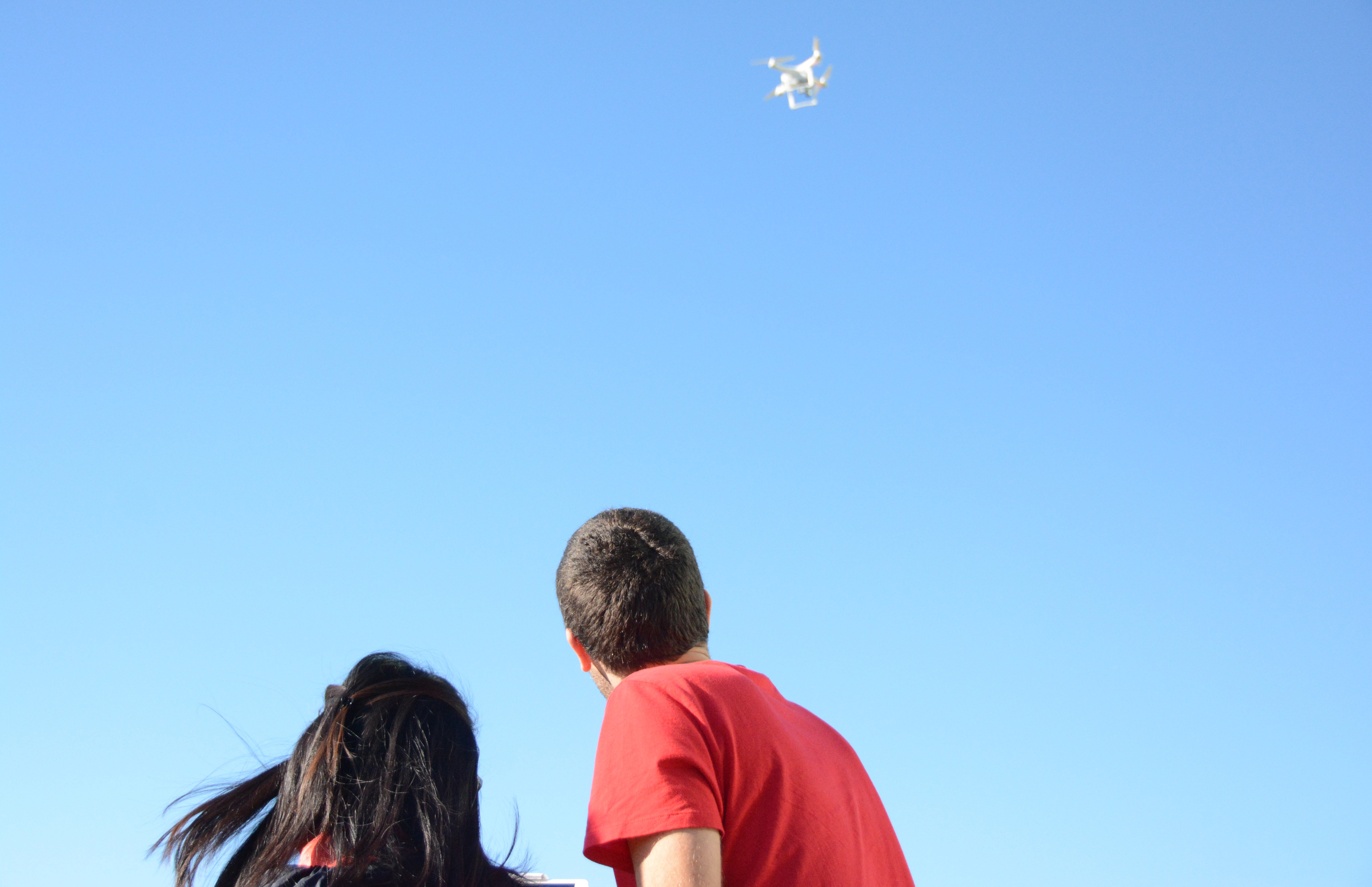 An undergraduate student and a PhD student fly a drone against a clear blue sky.
