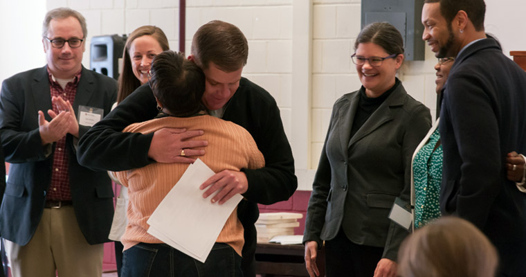 Graduate Eulah Rogers gets a hug from Boston Mayor Marty Walsh while Anne Douglass (right of mayor) looks on.