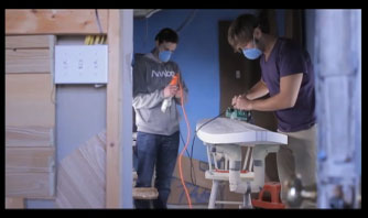 Two people sanding a surfboard