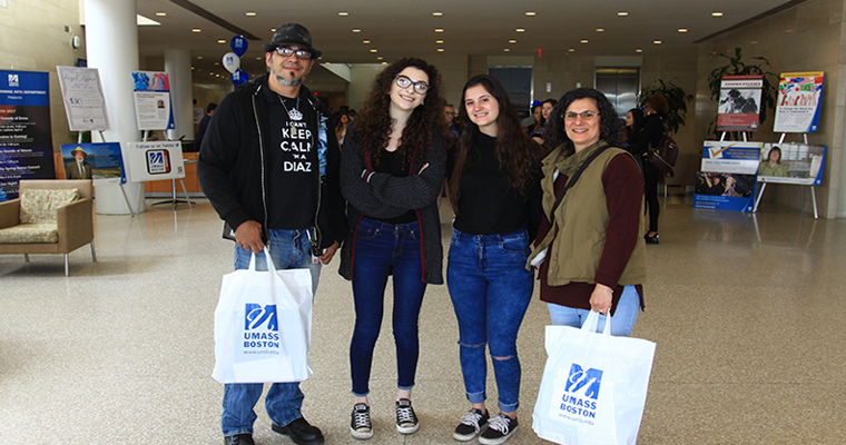Parents and prospective UMass Boston students hold UMass Boston bags