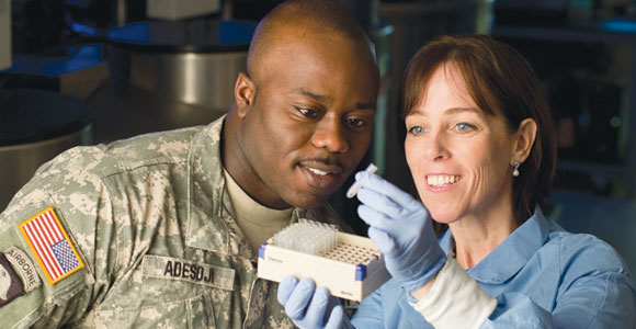 Cancer disparities researcher Julie Lynch '12 examples samples with Massachusetts Army National Guard Sgt. Dave Adesoji, a UMass Boston student.