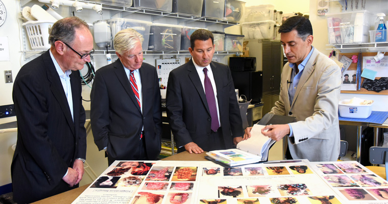Rafael Jaen (far right) gives a tour of the costume shop to Chancellor Barry Mills, President Marty Meehan and UMass Board of Trustees Chair