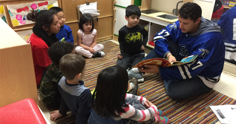 Freshman Dominic Blad reads to 4-year-olds at UMass Boston's Early Learning Center
