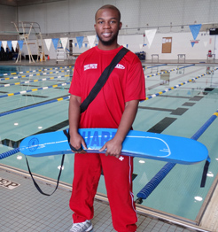 Lifeguard Chris stands in front of the swimming pool