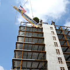 The final steel beam is raised into place above UMass Boston's first residence hall.